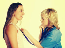 Nurse and Patient. Nurse using stethoscope on patient royalty free stock photo