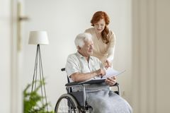 Nurse and patient in a wheelchair looking at photo album together and smiling. Concept stock images