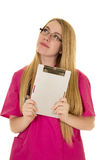 Nurse pink clothes and glasses hold clipboard look up Stock Photos