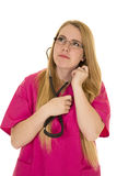 Nurse in pink outfit with stethoscope in ears look up Royalty Free Stock Photos