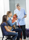 Nurse Playing With Dachshund While Woman And Daughter Smiling Royalty Free Stock Photos