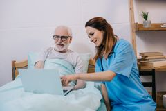 Nurse pointing at laptop in senior. Patient hands stock photos