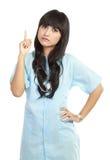 Nurse pointing something. Young nurse thinking and pointing something isolated on white background Stock Image