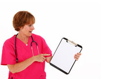 Nurse Pointing To Clipboard Royalty Free Stock Photos