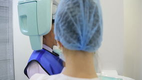 A nurse prepares a man of asian appearance to dental imaging. stock footage