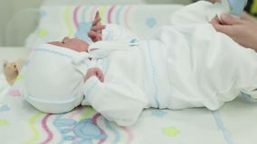 A nurse prepares a newborn baby to be discharged. Calm baby lying on the swaddling table stock video