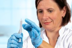 Nurse prepares a syringe for injection royalty free stock images