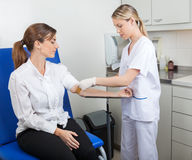 Nurse Preparing Businesswoman For Blood Test Stock Photo