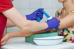 Nurse preparing patient to do a blood analysis by fixing garrot on her arm Stock Photography