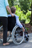 The nurse pushes the wheelchair of a disabled woman. The nurse pushes the wheelchair of a disabled women in the park Royalty Free Stock Photography