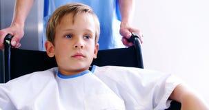 Nurse pushing boy in wheelchair stock footage