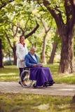 Nurse pushing elderly man in wheelchair while reading book. Nurse pushing elderly men in wheelchair while reading book in the park Stock Photo