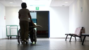 Nurse pushing a man in a wheel chair, backlighting. stock video