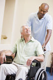 Nurse Pushing Man In Wheelchair Royalty Free Stock Images