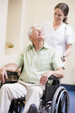 Nurse Pushing Man In Wheelchair Royalty Free Stock Photography