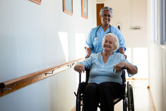 Nurse pushing patient sitting in wheelchair at nursing home. Portrait of nurse pushing patient sitting in wheelchair at nursing home Stock Photo