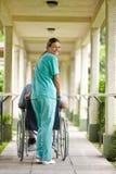 Nurse pushing senior man Stock Images