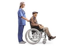 Nurse pushing a senior man sitting in a wheelchair royalty free stock photo