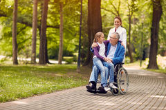 Nurse pushing senior man on wheelchair with his young granddaughter. Nurse pushing senior men on wheelchair with his young granddaughter in park stock photos