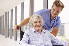 Nurse Pushing Senior Patient In Wheelchair Along Corridor Stock Photo