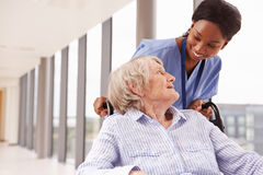Nurse Pushing Senior Patient In Wheelchair Along Corridor Royalty Free Stock Photography