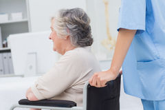 Nurse pushing senior patient in wheelchair at clinic Stock Image