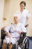 Nurse Pushing Senior Woman In Wheelchair Royalty Free Stock Image