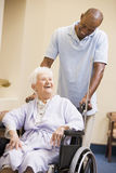 Nurse Pushing Senior Woman In Wheelchair Stock Image