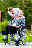 Nurse pushing senior woman in wheelchair on walk Stock Images