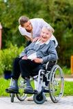 Nurse pushing senior woman in wheelchair on walk Stock Images