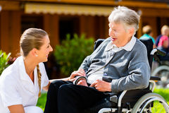 Nurse pushing senior woman in wheelchair on walk Royalty Free Stock Photography