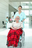 Nurse pushing a wheelchair Royalty Free Stock Image