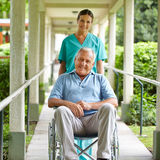 Nurse pushing wheelchair Stock Photography