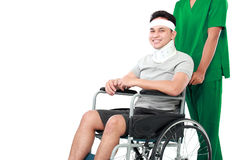 Nurse pushing young patient in wheelchair Royalty Free Stock Images