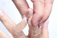 Nurse putting adhesive bandage on elderly hand Royalty Free Stock Photo