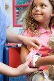 Nurse putting bandage on girl Royalty Free Stock Photography
