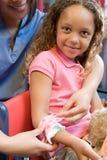 Nurse putting bandage on girls arm Royalty Free Stock Photos