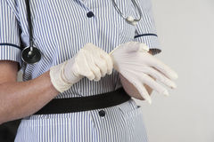 Nurse putting on surgical gloves Stock Images