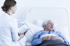 Nurse reading book to patient. Female nurse reading book to senior patient in hospice Stock Photography