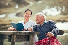 Nurse reading book to senior man outdoor. Smiling nurse reading book to senior men outdoor Royalty Free Stock Photos