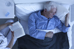 Nurse reading for senior patient. Nurse reading for lonely and suffering patient in hospital room Stock Images