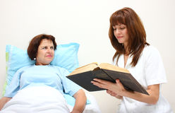 A nurse reading to a patient Royalty Free Stock Photography