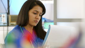Nurse reviews the chart of patient test results Stock Photo