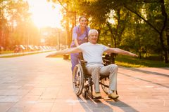 A nurse is standing behind an old man, who is sitting in a wheelchair and placed his arms like wings. The nurse rolls the old men who is sitting in a wheelchair Stock Photos