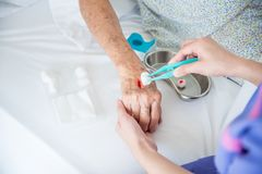 Nurse`s hands dressing wound for patient`s hand Stock Photo