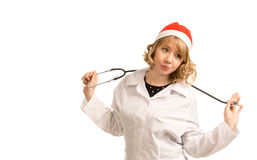 Nurse in a Santa Hat. Pretty young blonde nurse in a Santa Hat celebrating Christmas playing with the stethoscope around her neck isolated on white stock image