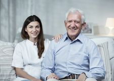 Nurse and senior man. Nurse and senior men sitting on the sofa Stock Photos