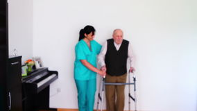 Nurse and senior man using walking frame Stock Images
