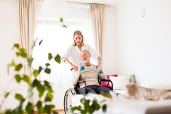 Nurse and senior man in wheelchair during home visit. Health visitor and a senior men in a wheelchair during home visit. A nurse or a physiotherapist helping a Royalty Free Stock Photo