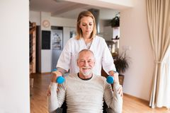 Nurse and senior man in wheelchair during home visit. Health visitor and a senior men in a wheelchair during home visit. A nurse or a physiotherapist helping a Royalty Free Stock Photos